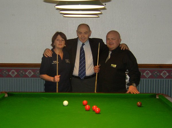 Husband and wife pupils stood at snooker table with coach